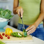 mid section view of a woman cutting vegetables